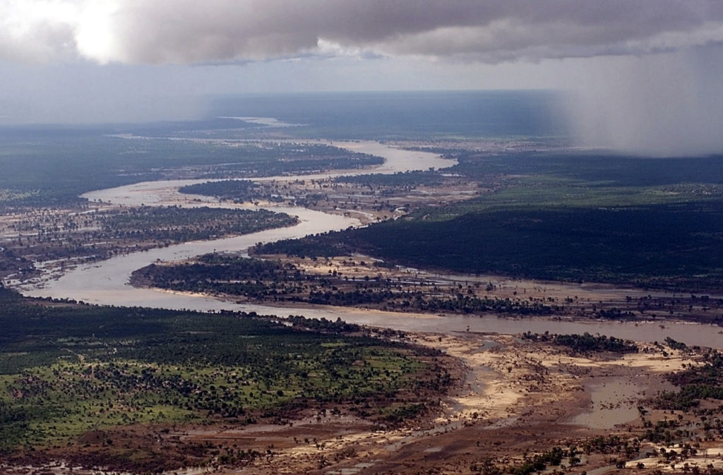 Aerial view, extreme long shot, looking down as the Limpopo River winds its way through Southern Mozambique, where it recently crested its banks and sent floodwaters rushing through towns and farmland,  forcing people from their homes and wreaking havoc with the countries infrastructure.  Even though waters have receded over the past week, heavy rains seen in the distance, continue to threaten the region with more flooding.  C-130 aircraft (not shown), assigned to the 37th Airlift Squadron at Ramstein Air Base, Germany, fly daily Keen Sage aerial surveillance missions  over Mozambique to help find stranded flood victims and survey flood levels and damage caused by the flooding in Southern Africa.  The 37th Airlift Squadron C-130 aircraft, are deployed to Hoedspruit Air Force Base, South Africa, as part of the United States Operation Atlas Response, humanitarian relief efforts.