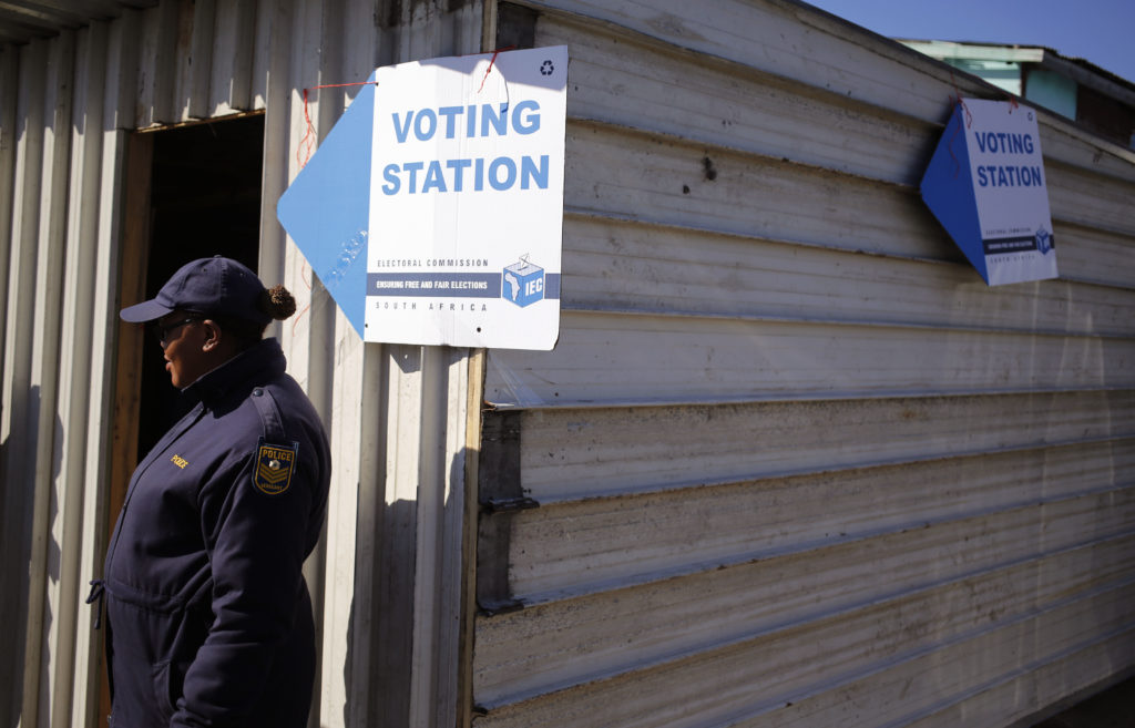 A South African policewoman provides security outside a polling station opened for voting by the elderly and disabled for the municipal elections in the township of Khayelitsha on the outskirts of Cape Town, South Africa, Tuesday, Aug. 1, 2016. South Africa's ruling party faces a robust challenge in municipal elections on Wednesday from opposition groups seeking to capitalize on scandals linked to President Jacob Zuma. (AP Photo/Schalk van Zuydam)